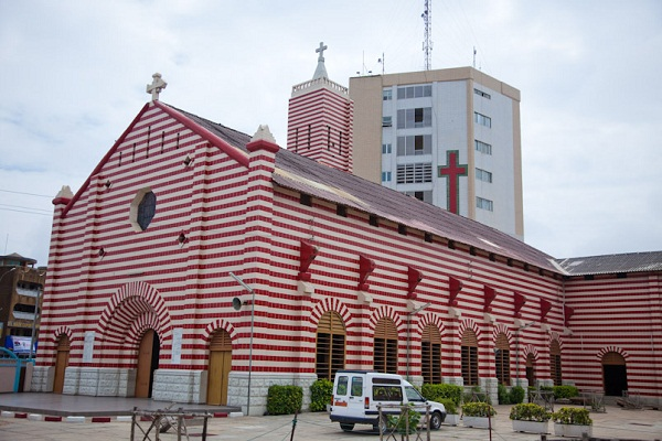 The distinctive Notre Dame Roman Catholic cathedral, Notre Dame des Apotres, in Cotonou, Benin, stands out for its red and white striped exterior.
