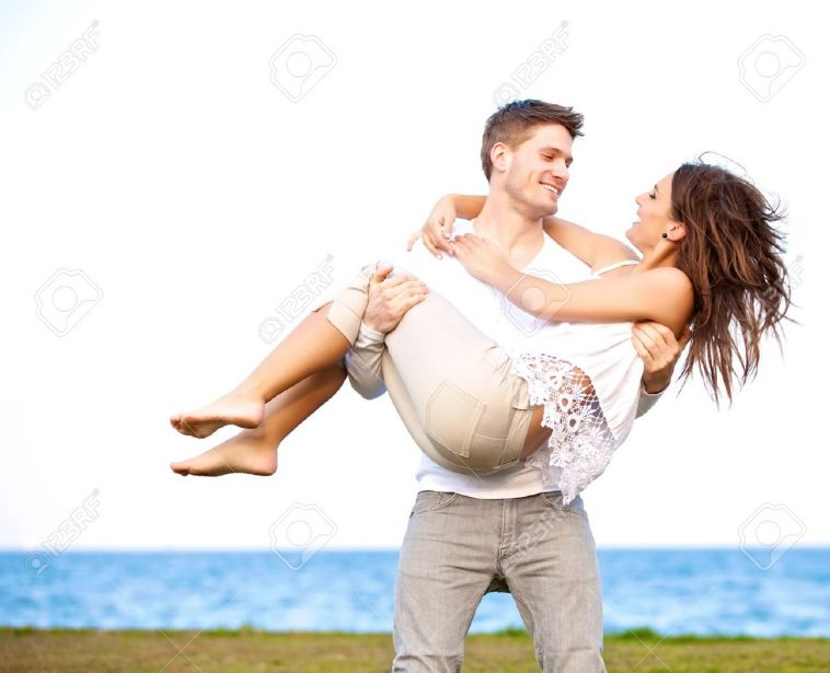 14679912-Portrait-of-a-guy-carrying-his-beautiful-girlfriend-in-a-windy-beach-Stock-Photo