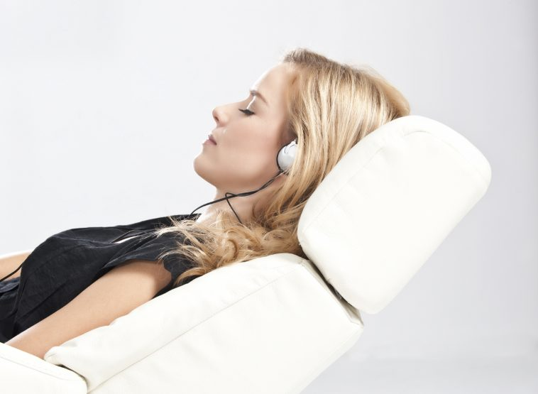 Blond woman listening to music  and relaxing on sofa