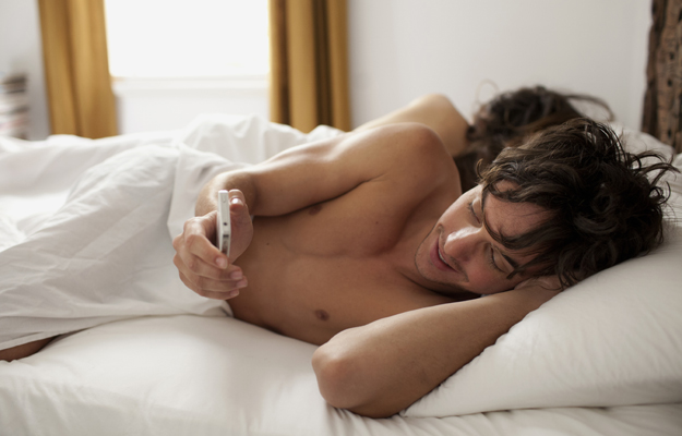 Couple in bed man cheating on mobile sms
