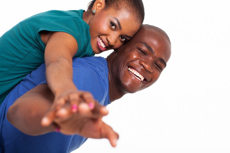 happy young african woman enjoying piggyback ride on boyfriends back with their hands outstretched