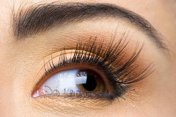 Female eye with gold make-up and long eyelashes