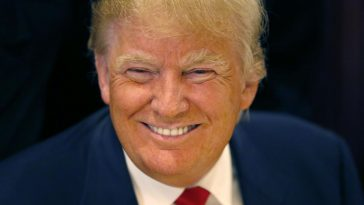 FILE - In this June 29, 2015, file photo, Republican presidential candidate Donald Trump smiles for a photographer before he addresses members of the City Club of Chicago, in Chicago. As other presidential candidates fight to raise money, Trump is reminding everyone he's already got a lot of it. The celebrity businessman's campaign was expected to reveal details on July 15 of his fortune, which he estimated last month at nearly $9 million when announcing his Republican presidential candidacy. (AP Photo/Charles Rex Arbogast, File)