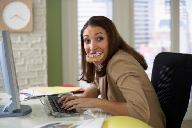 Woman-eating-a-donut-at-her-computer-78715216-Credit-Fuse-630x420