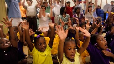 Memphis University School students line up at the back of the class to learn a new song during chapel time at Perea Preschool in in Memphis, Tenn. Wednesday, Sept. 18, 2013. The group of 35 MUS boys visiting Perea to tutor and entertain the kids was one of several civic service projects by MUS students on Wednesday. One group of students volunteered to clean up along the Wolf River while others helped out with MIFA Meals on Wheels.  (AP Photo/The Commercial Appeal, Jim Weber)