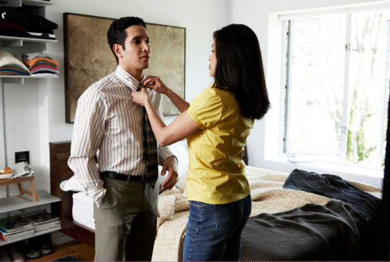 Latino couple dressing in bedrom