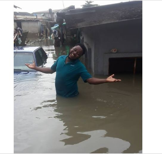 Nigerian Man Smiling Outside His Flooded Home