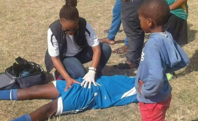 Female Medical Personnel Attending To An Injured Player During Match
